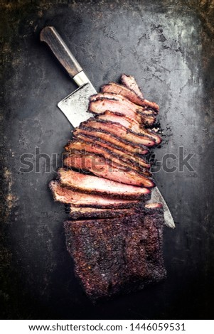 Traditional smoked barbecue wagyu beef brisket offered as top view with a knife on an old rustic board with copy space