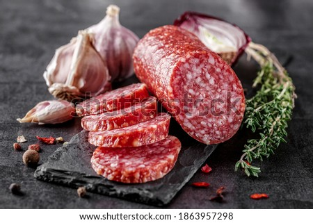 Traditional smoked salami sausage with spices.Salami sausage slices on a black chopping Board. Dark background. Сток-фото ©