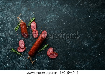 Traditional smoked salami sausage with spices. Slice sausages. Rosemary. Top view. Free space for your text. Сток-фото ©