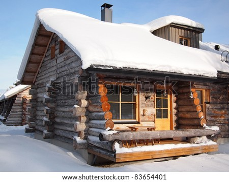 Traditional snow covered log cabin in a holiday resort in Lapland, Finland.