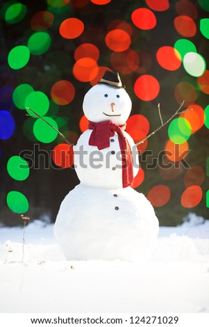 Traditional snowman wearing red scarf and black hat with carrot nose, colorful lights blurred on background