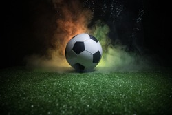 Traditional soccer ball on soccer field. Close up view of soccer ball (football) on green grass with dark toned foggy background. Selective focus