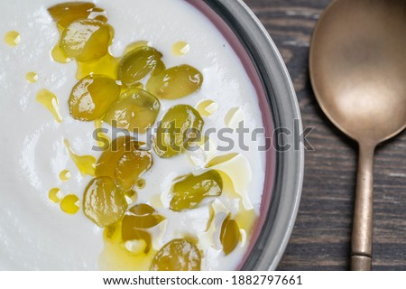 Traditional Spanish dish, cold soup ajo blanco or ajoblanco from garlic, almonds, white wine vinegar, olive oil and green grapes in a bowl with a spoon, close up Stockfoto ©