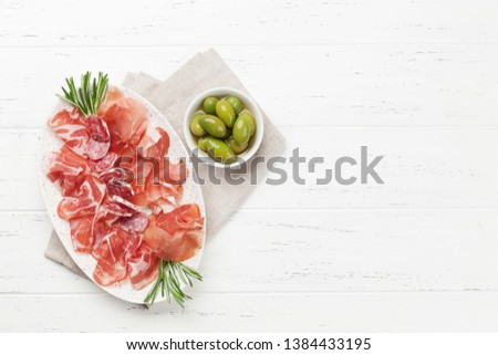 Traditional spanish jamon, prosciutto crudo, italian salami, parma ham. Antipasto plate and olives. Top view flat lay. With copy space Сток-фото ©