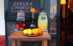 Traditional spanish sangria and limonada. Sangaree and limonade jar with colorful fruits, oranges and lemons on a typical mediterranean bar in Seville, Andalusia. Spanish wine, food and drink.