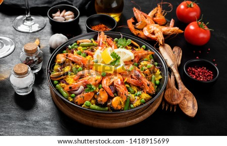 Traditional spanish seafood paella in the fry pan on a black wooden  table.