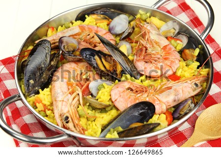 Traditional Spanish seafood paella with king prawns, mussels and clams on a red checkered tablecloth - stock photo