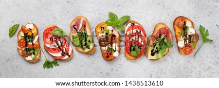 Traditional spanish tapas with tomatoes, mozzarella cheese, avocado and prosciutto on stone background. Flat lay. Top view Foto stock ©