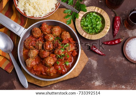Traditional spicy meatballs in tomato sauce with garnish on a concrete background. Selective focus.