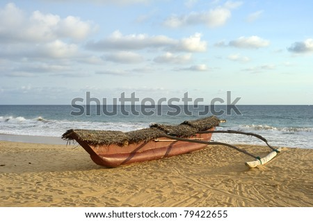 Traditional sri lankan fishing boat on ocean beach at sunset