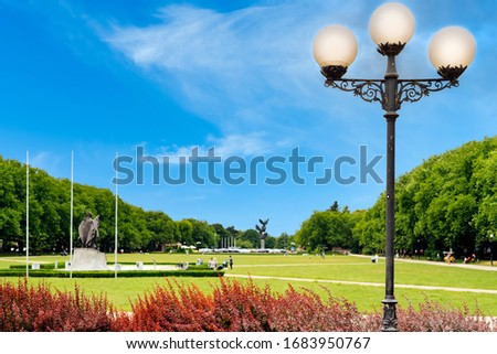 Traditional street lamppost with 3 shades near Szczecin City Council. Blurred Jasne Blonia square with pope monument and people relaxing in background Zdjęcia stock ©