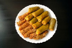 Traditional stuffed squash and cabbage rolls on white plate on dark wooden background. Famous traditional Middle East, Egyptian, Asian cuisine. Mahshi or mahshy, stuffed vegetables.