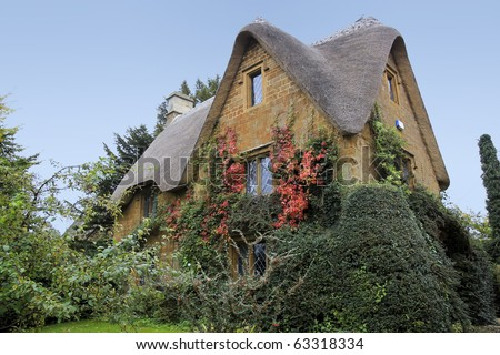 traditional style cotswalds thatched roof stone cottage in oxfordshire england
