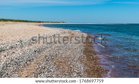 traditional sunny summer landscape with sandy and pebbly promontory, blue sea and sky, Harilaid Nature Reserve, Estonia, Baltic Sea
