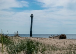 traditional sunny summer landscape with sandy and pebbly promontory, green dune grass, abandoned sloping Kiipsaare lighthouse in background, Harilaid Nature Reserve, Estonia, Baltic Sea