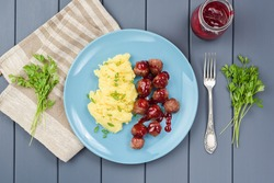 Traditional Sweden meatballs with berry sauce and mashed potatoes served with parsley and linen cloth above view