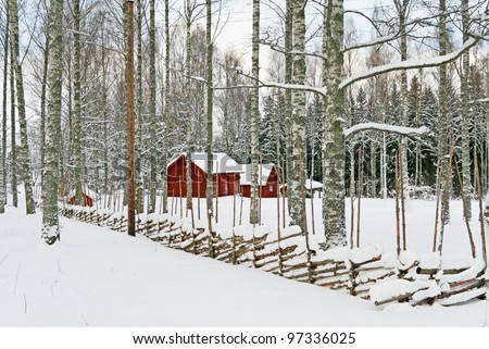 Traditional Swedish red wooden houses in a snowy landscape.