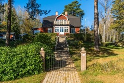 Traditional Swedish wooden house villa cottage red color. Two storey country house with balcony. Metal cast gate entrance to courtyard with two decorative stone pillars. Stony path and high staircase.