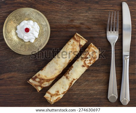 Traditional sweet pancakes on wooden plate. Two fried folded pancakes with cheese stylish saucer decorated white cream with red berry folk and knife rough country wood background