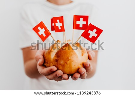 Traditional swiss bread buns called in German 1.Augustweggen baked in Switzerland to celebrate Swiss National Day on August 1st. Body parts, children hands holding bread. Swiss flags on toothpicks.