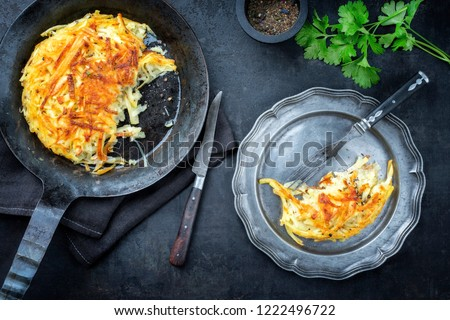 Traditional Swiss rosti as side dish with leek as top view in a frying pan and a pewter plate  #1222496722