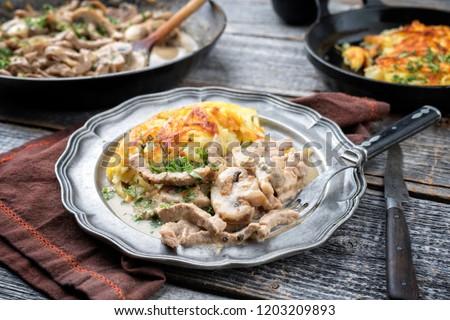 Traditional Swiss zürcher geschnetzeltes with rösti as closeup in a pewter plate  #1203209893