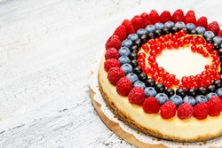 Traditional tasty raspberry and blueberry cheesecake on wooden table