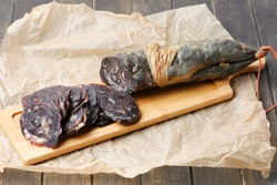 Traditional Tatar (Kazakh, Bashkir, Turkic, Uzbek) Food Dried Horse Meat Sausage - Kazy, Kazylyk Sliced On Board, Baking Paper, Wooden Background. Top View, Copy Space.