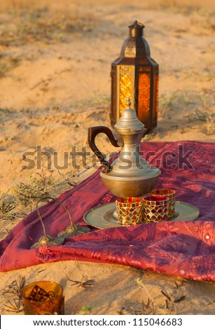 Traditional tea set and lamp on desert sand