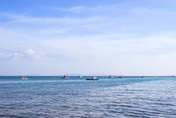 Traditional thai fishing boat floating in the sea of thailand near koh larn on day the bright sky.