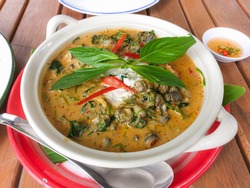 Traditional Thai food, Thaicurrywith riversnail , betel leaves and climbimg wattle in coconut milk, decorated with red chili and basil.