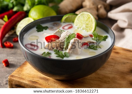 Traditional Thai food Tom Kha Gai in bowl and ingredients on wooden table Foto stock ©