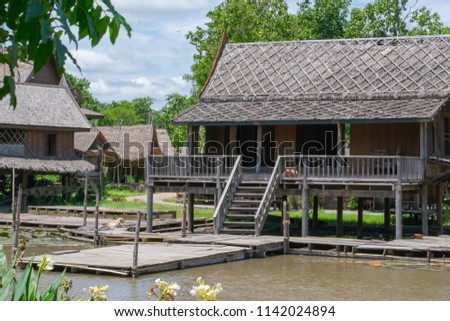 Traditional Thai house. Thai style wooden house made from bamboo or wooden structure. House for a single family and includes bedroom and kitchen. House built near the coast or a river for travel. #1142024894