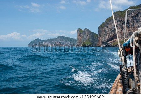 Traditional Thai Longtail boat and island of Phi Phi Leh on the horizon,Thailand