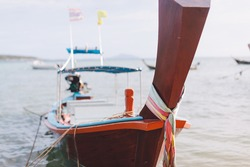 Traditional Thai wooden longtail boat close up photo. Bow of Long Tail Boat with beautiful color. Fishing boat bow on blue sky and sea beach background with copy space. Holiday concept