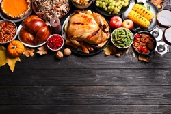 Traditional Thanksgiving day feast with delicious cooked turkey and other seasonal dishes on black wooden table, flat lay. Space for text