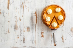 Traditional thanksgiving food concept. Orange delicious homemade pumpkin pie with crust on grunged wood textured table. .Top view, close up, copy space, background.