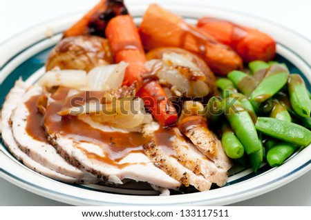traditional Thanksgiving or Christmas turkey dinner with crispy skin, turkey slices and fresh roasted  vegetables smothered in gravy