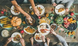Traditional Thanksgiving or Friendsgiving holiday celebration party. Flat-lay of friends feasting at Thanksgiving Day table with turkey, pumpkin pie, roasted seasonal vegetables and fruit, top view