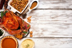 Traditional Thanksgiving turkey dinner. Top view side border on a rustic white wood background with copy space. Turkey, stuffing, mashed potatoes and pumpkin pie.