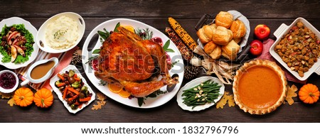 Traditional Thanksgiving turkey dinner. Top view table scene on a dark wood banner background. Turkey, mashed potatoes, dressing, pumpkin pie and sides.