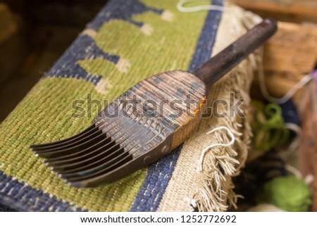 Traditional tibetan сarpet workshop of Tibetan Refugee Self Help Center, Darjeeling, India. Wooden tool used in weaving of carpets.