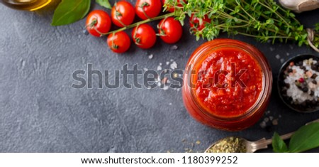 Traditional tomato sauce in a glass jar with fresh herbs, tomatoes and olive oil. Top view. Copy space. Slate background.