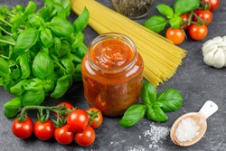 Traditional tomato sauce in a glass jar with fresh herbs, tomatoes, spaghetti, coarse salt and basil. Dark background, side view.