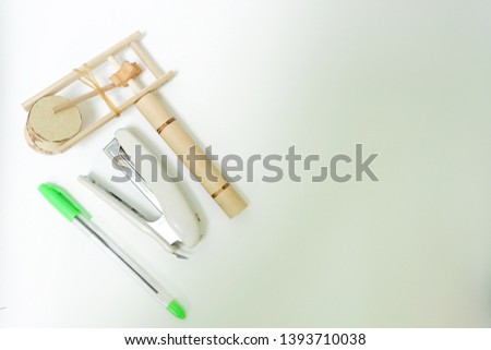 Traditional toy made from bamboo (klotokan/otok-otok), pens and stapler isolated on white background. Top view close up details.