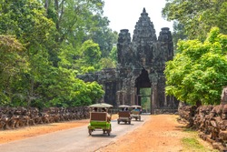 Traditional Tuk Tuk on a road and South gate to Angkor Thom, near Siem Reap, Cambodia in a summer day