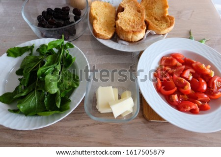 Traditional Turkish breakfast including egg bread, sliced tomato and olive oil, Fresh green rocket salad, black olives, cheese, green peppers, and salt.It is called 'Yumurtali Ekmek', 'Roka Salatasi' Stok fotoğraf ©
