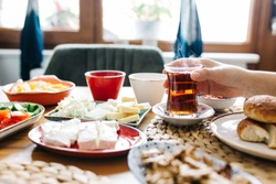 Traditional Turkish Breakfast with Turkish Tea & Bagel (simit). A woman is holding tea at breakfast (selective focus)