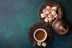 Traditional turkish coffee  and turkish delight on dark green wooden background. Flat lay.