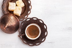 Traditional turkish coffee and turkish delight on white shabby wooden background. Flat lay